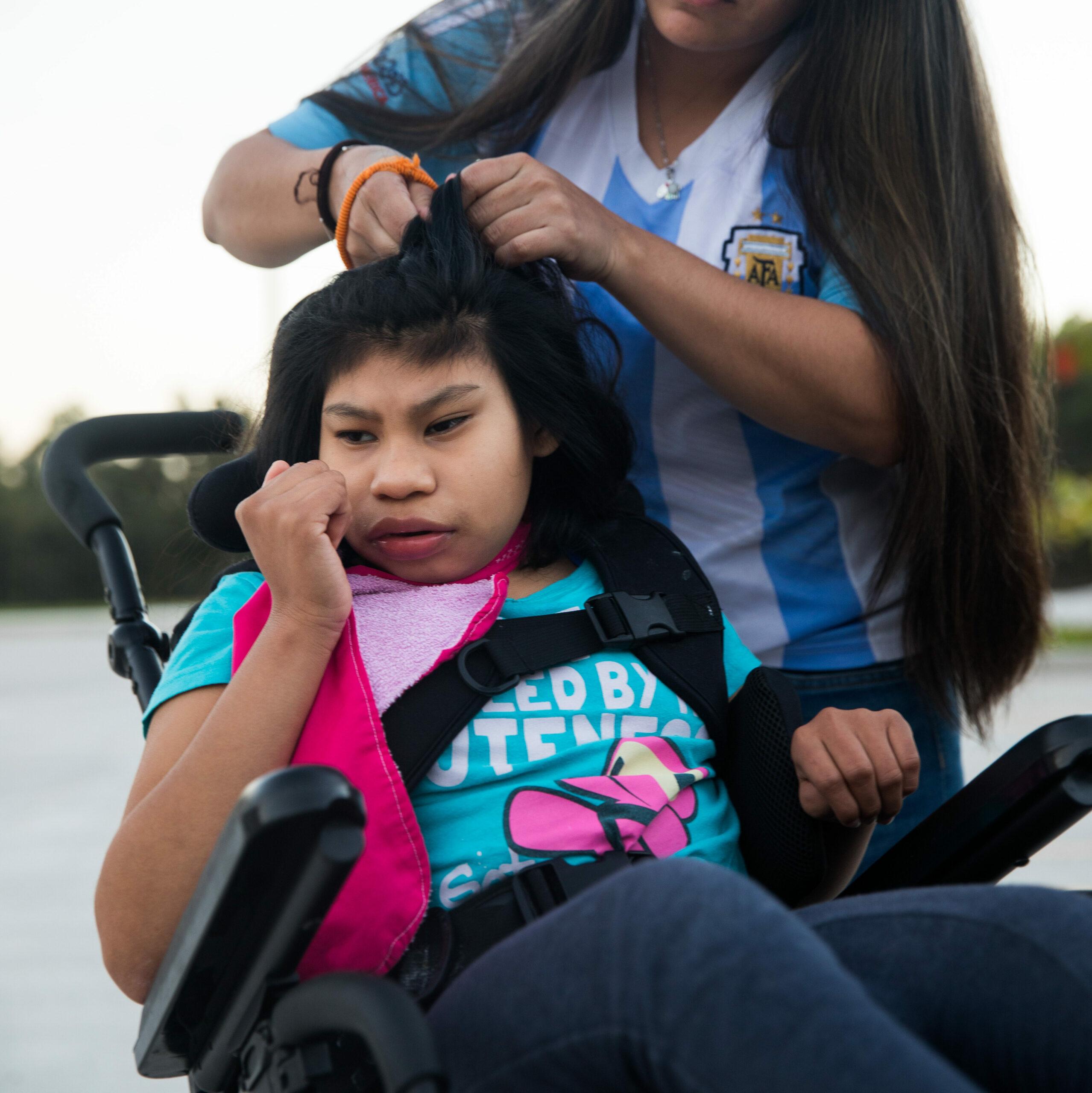 Ein Kind imRollstuhl erhält eine Frisur von einem anderen Mädchen.