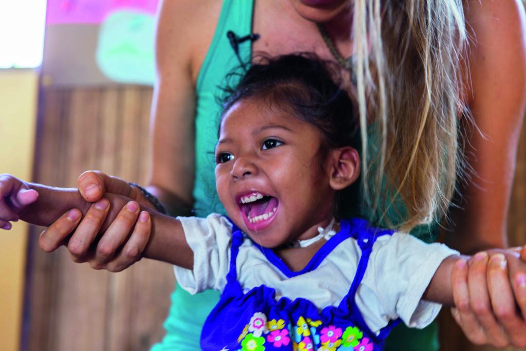 kleines lachendes Mädchen mit Behinderung bei der Therapie