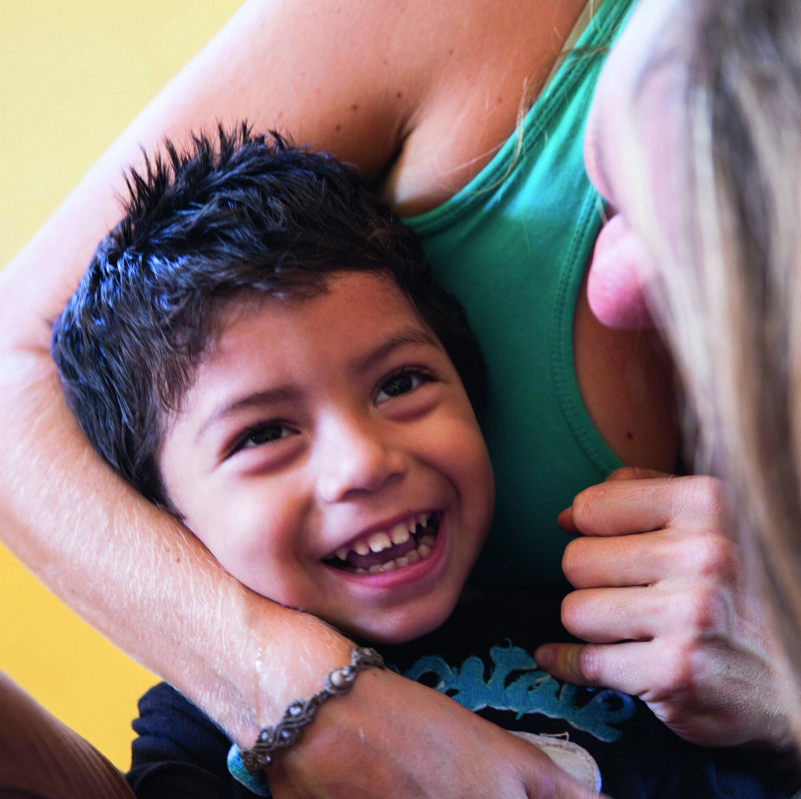 lachender Junge mit Behinderung bei der Therapie