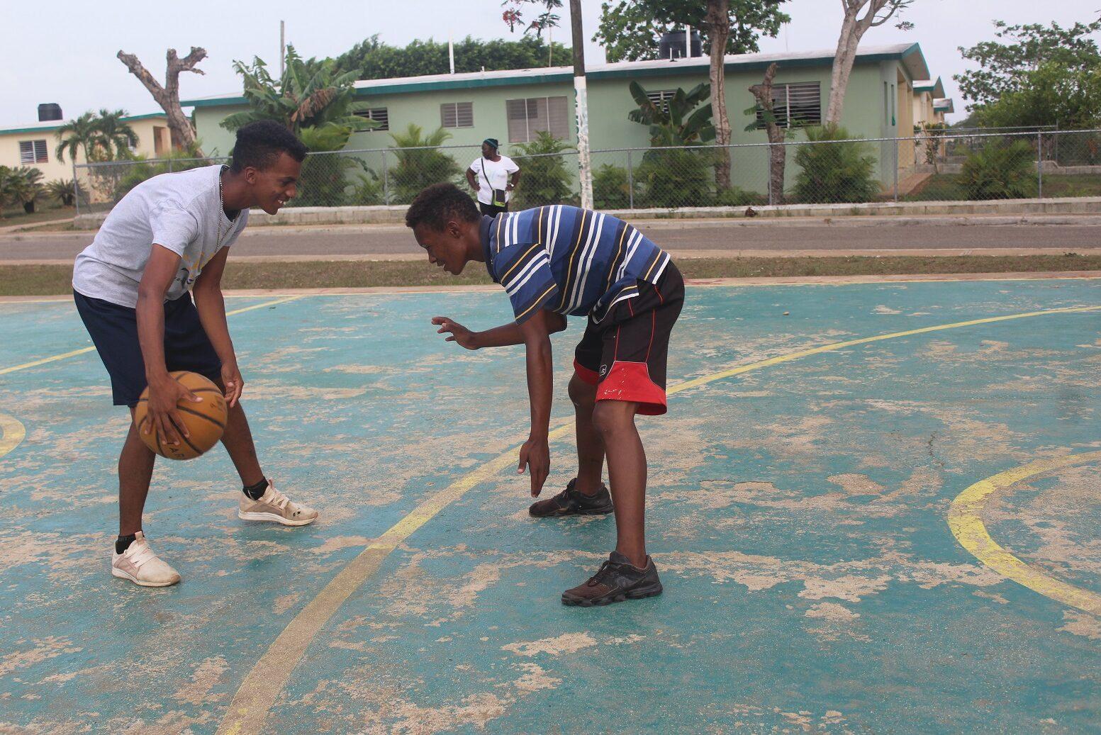 Zwei Knaben spielen Basketball.