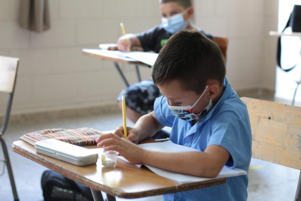 Ein Schüler schreibt in seinen Block