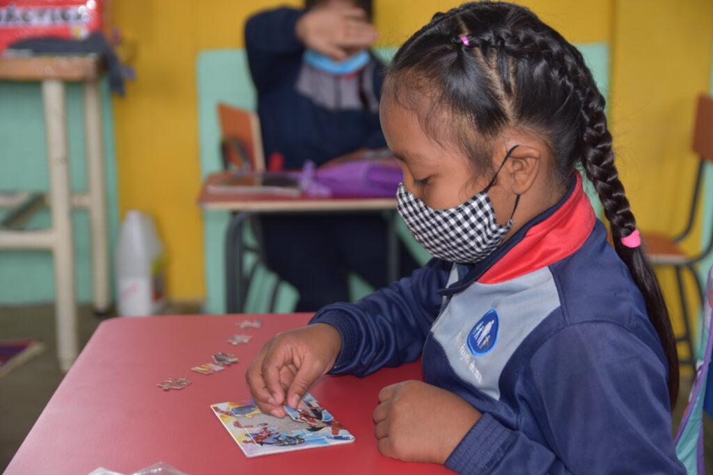 Eine Schülerin bei NPH Guatemala löst ein Puzzle